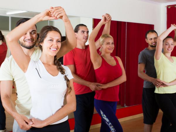 Group of adult american people dancing salsa in studio