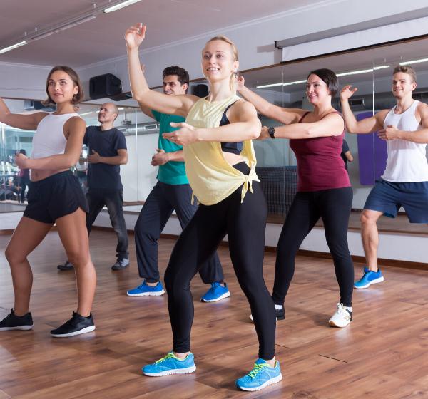 Cheerful ordinary adults dancing bachata in dance studio