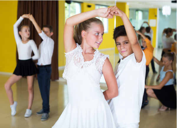 Boys and girls learning new pair dances with young female trainer in dance hall