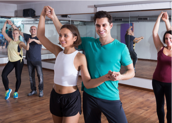 Smiling adults dancing together in dance class
