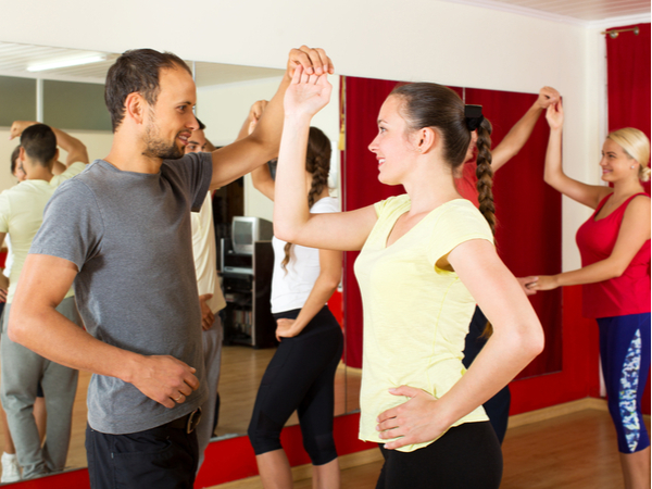 Positive young people dancing Latino dance in class