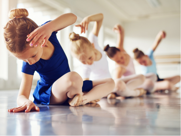 Little ballerinas doing exercises and bending sitting on floor in ballet class.