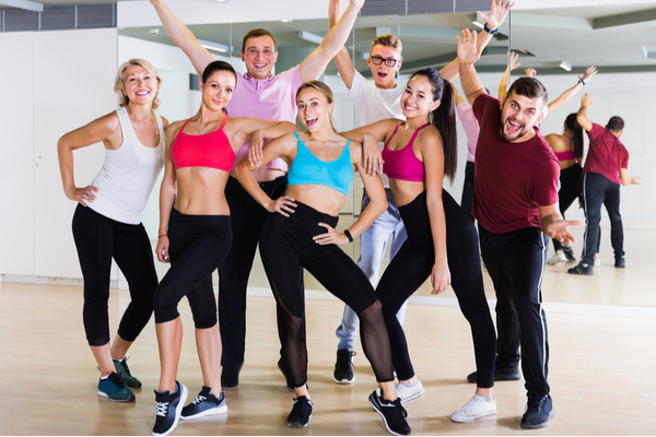 Modern males and females dancing excited posing in studio