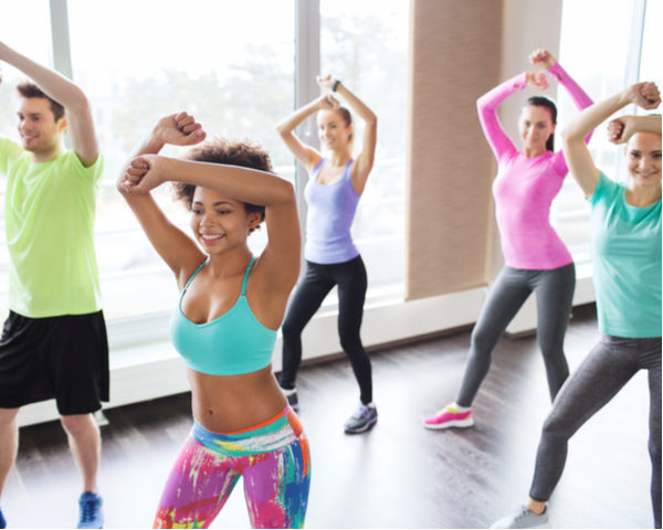 Group of smiling people with coach dancing zumba in gym or studio